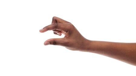 Schwarze weibliche Hand, die eine kleine Menge von etwas zeigt und unsichtbare Gegenstände misst, isoliert auf weißem Hintergrund. Panorama mit Kopienraum