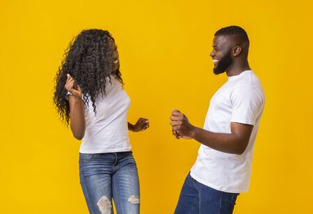 Sweet black couple having good time, dancing and fooling, yellow background