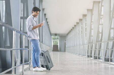 Onlineanmeldung. Junge Passagiere vernetzen sich auf dem Handy, warten auf das Boarding am Flughafen, leerer Raum Standard-Bild