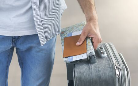 Travel concept. Man going to flight with suitcase, passport and airline ticket, close up 版權商用圖片