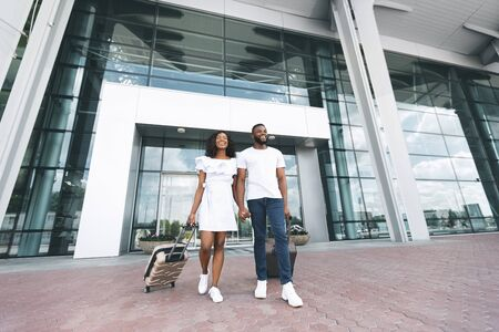 Happy millennial black couple enjoying new destination, standing at aiport building, empty space