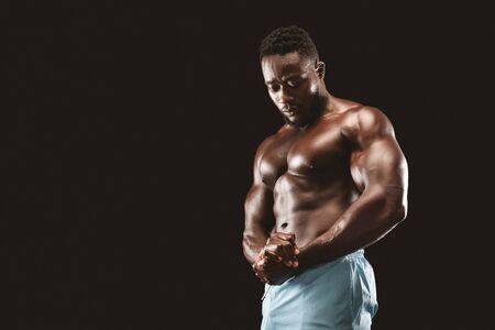 Culturista africano flexionando los músculos del pecho, mostrando bíceps en estudio, fondo negro, espacio de copia