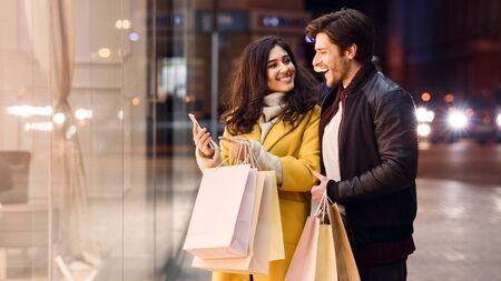 Jeune couple avec des sacs à provisions et un smartphone, debout près de la vitrine du magasin le soir