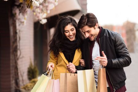 Happy couple looking into shopping bags, examining purchases outdoors Фото со стока - 129940201