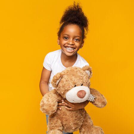 Lieblingsspielzeug. Nettes afrikanisches Baby, das mit ihrem Teddybären lacht, gelber Studiohintergrund