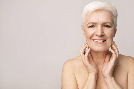 Retrato de mujer mayor atractiva tocando su barbilla y mirando a la cámara sobre fondo de estudio claro, espacio libre