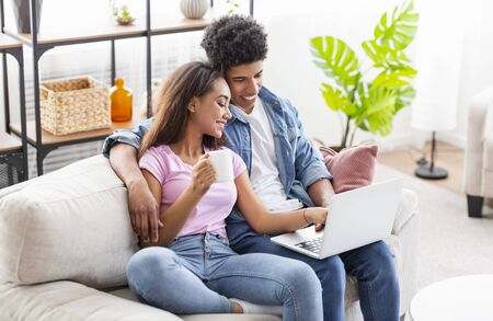 Couple of black teenagers using laptop together while sitting on couch at home, girl drinking coffee 스톡 콘텐츠 - 129940296