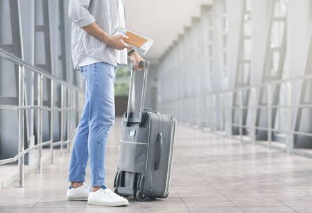 Start of travel. Male tourist with luggage and boarding documents waiting for flight at airport, free space