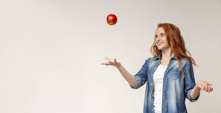 Happy beautiful redhead girl throwing apple in the air on light studio background, panorama with copy space