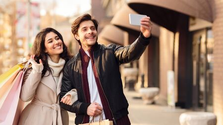 Consumerism concept. Young couple taking selfie near boutiques outdoors