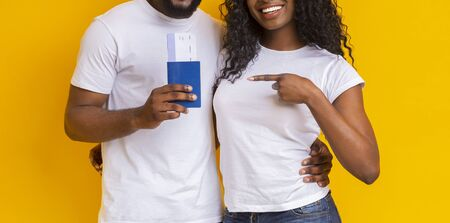 Traveling and tourism concept. Black couple holding passport with tickets, posing over yellow studio background, cropped Stock Photo