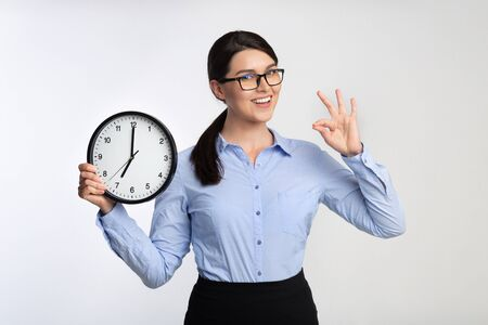 Meet Deadline. Positive Businesswoman Holding Clock Gesturing OK On White Studio Background. Foto de archivo - 129940462