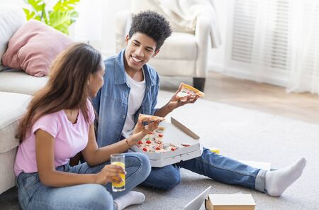Student couple eating pizza and having drinks, sitting on floor while studying at home