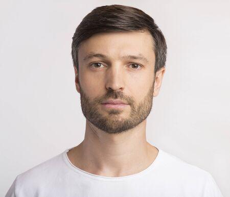 Ausweisfoto. Porträt des Mannes mittleren Alters, der Kamera über weißem Studiohintergrund betrachtet. Isoliert