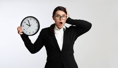 Deadline. Shocked Businesswoman Holding Clock Clutching Head Being Late For Work On White Background In Studio Foto de archivo - 129940221