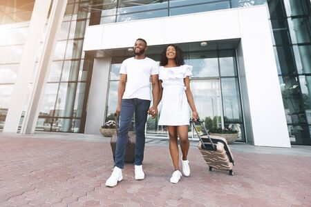 Happy black couple going with luggage out of airport building, free space