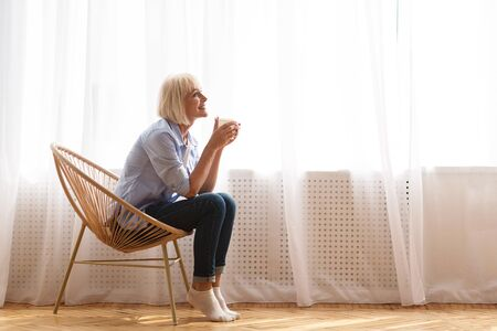 Senior woman sitting on chair in front of window and drinking tea, side view, copy space Stock fotó