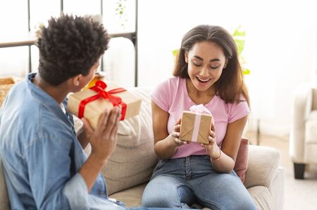 Happy african american couple exchanging gifts with each other at home, girl delighted