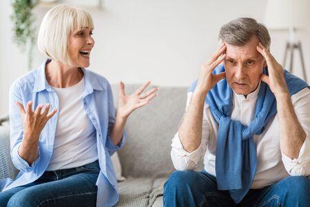 Angry senior woman shouting at upset man, quarreling at home. Man having headache