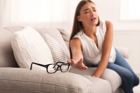 Eyesight Problem. Young Woman Reaching Hand For Eyeglasses Having Bad Eye Sight Sitting On Couch At Home. Selective Focus