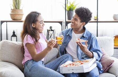 Happy black couple eating pizza and having drinks on a date at home
