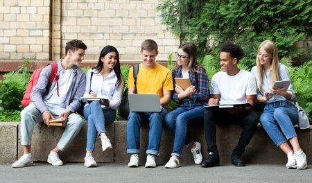 Bildungskonzept. Glückliche Teenager, die sich mit Büchern und Laptop auf Prüfungen auf dem Universitätscampus vorbereiten Standard-Bild