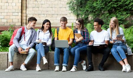 Education concept. Happy teens preparing for exams in university campus with books and laptop