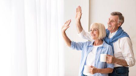 Couple de personnes âgées agitant les mains près de la fenêtre, disant au revoir aux petits-enfants, espace libre