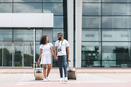Travel and tourism. Black couple going out of airport building with luggage, free space