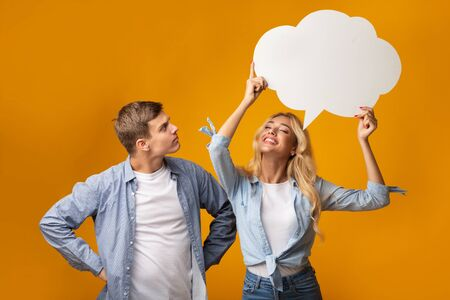 Happy blonde girl holding speech bubble over her head, curious guy trying to guess what she thinking. Copy space