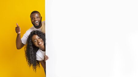 Black Girl And Guy Holding White Advertising Board, guy showing thumb up, yellow studio background, panorama