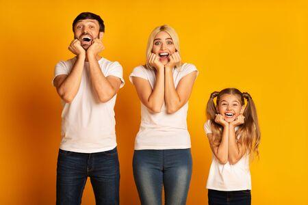 Wow. Surprised Family Of Three Posing Touching Cheeks Over Yellow Studio Background. 写真素材