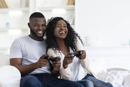 Young African American Couple Playing On Game Console With Joysticks, Copy Space