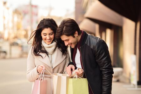 Young couple checking their purchases, looking into shopping bags after shopping in boutiques Фото со стока - 129941080