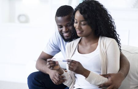 Young black couple happy about positive results of pregnancy test, hugging each other, copy space
