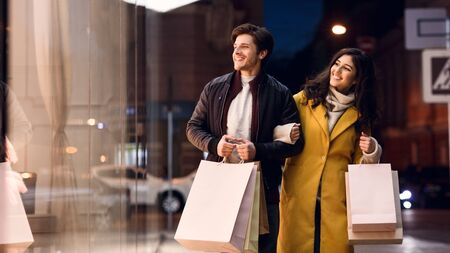 Happy couple after successful shopping, walking outdoors in the evening, panorama