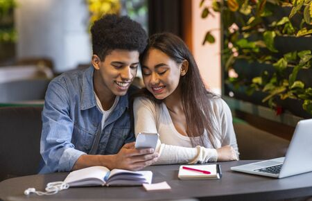 Helpful mobile application. Mixed race happy student couple making homework on laptop in cafe, looking at cellphone, copy space Stock Photo