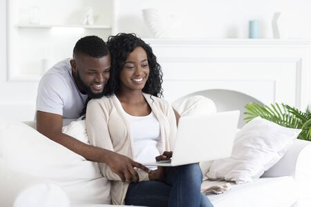 African american couple using laptop making video call to their parents, copy space Stock Photo