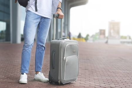 Waiting for cab. Millennial man standing with luggage at airport exterior, empty space