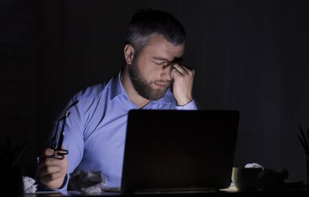 Exhausted Middle Aged Bearded Businessmen Working With Laptop In Dark Room, overworking, copy space 版權商用圖片