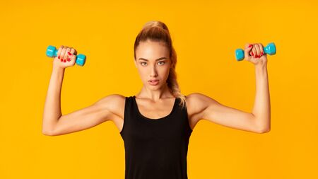 Workout. Determined Young Lady Exercising With Dumbbells On Yellow Background. Studio Shot, Panorama