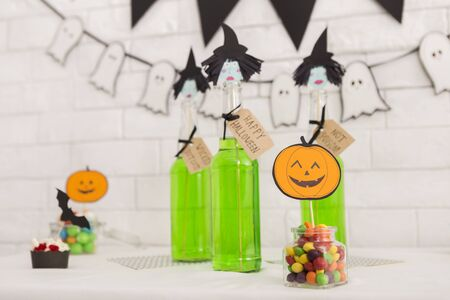 Happy halloween. Green party drinks with decorations and pumpkins on background