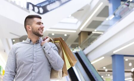 Handsome guy with purchases waiting for girlfriend in shopping center, copy space