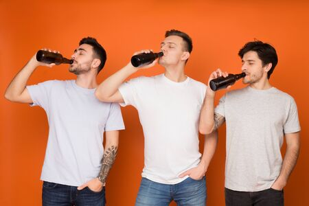 Three mates drinking beer from bottles, standing in row over orange background