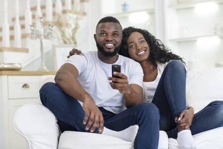 Glückliches tausendjähriges Paar umarmt und sieht fern, sitzt auf dem Sofa im Wohnzimmer
