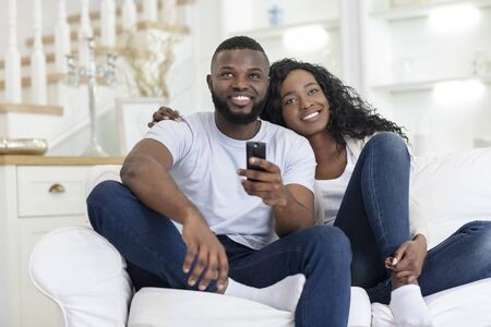 Happy Millennial Couple Embracing And Watching TV, Sitting On Sofa In Living Room