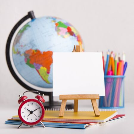 Time to school. Close up of easel and office stationery on white background