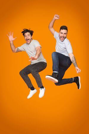 Crazy guys jumping and having fun over orange studio background, crop Stockfoto