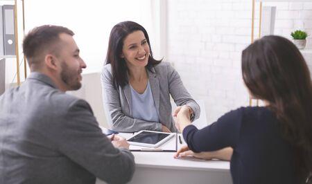 Trato. Corredor de seguros positivo apretón de manos con pareja joven después de firmar el contrato de acuerdo