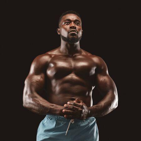 Retrato de guapo deportista africano musculoso demostrando su cuerpo sobre fondo negro de estudio, flexionando los músculos del pecho Foto de archivo